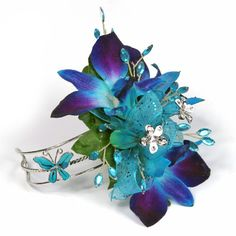 Dendrobium orchids, rhinestone flower jewels, glittered turquoise ribbon and a butterfly wristlet cuff = unique!