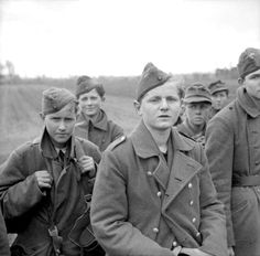 """Caption: """"Young German Wehrmacht soldiers are photographed after capture by the British Army's 11th Armoured Division. Their expressions run the gamut from defiance, fear and relief. Towards the end of the war, with so many able-bodied German men depleted from the pool of conscripts, it wasn't uncommon to find German boys as young as 12 or 14 on the frontlines. Levern, North Rhine-Westphalia, Germany. 4 April 1945. """""""