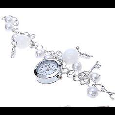Beautiful silver charm bracelet with Quartz watch. White beads, silver keys and a Quartz watch are all a part of this beautiful charm bracelet. Jewelry Bracelets