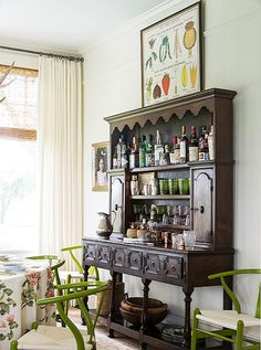 Since the kitchen is on the petite side, Bailey uses the dining room's vintage hutch as a bar and serving station.