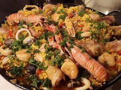 Paella met kip, chorizo, kabeljauw en gamba's.