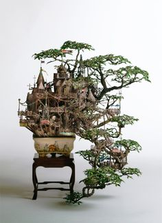 """""""Bonsai-B"""" by Takanori Aiba  Cultivating a modern Bonsai style by adding a theme of relationship between human and nature to a Japanese classical Bonsai style. Originally, Japanese Classical Bonsai Style portraits the beauty of nature in miniature. Bonsai-B is an experimental approach to turn out a modern Bonsai style that portraits the beauty of spiritual accordance between human and nature in miniature.  Mixed Media, 16.5″x 14.5″x 18.9″, 2005"""