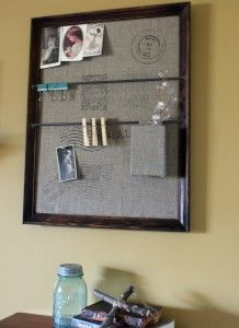 Pottery Barn Wall Organizer: cover a bulletin board with burlap, and attach dowel rods into the frame.