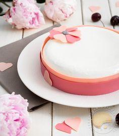 Délicat entremets pour la fête des mères composé d'un macaron géant aux biscuits roses surmonté d'une ganache montée au chocolat blanc parfumée à l'amande amère et garni d'une compotée de cerises le tout recouvert d'un nappage neutre et décoré de chocolat rose.