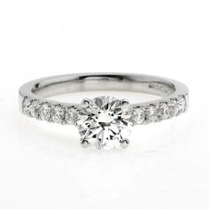A round brilliant cut diamond solitaire ring, of 1.01cts, certified H colour VS2 clarity, mounted in a platinum claw setting with diamond shoulders, combined weight 0.30ct. HRD certificate.