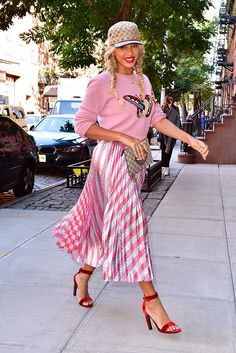 Beyoncé bringing out her girlie side in a bubblegum pink, butterfly-emblem sweater and metallic pleated midi skirt. The logo-heavy Gucci clutch and cap keep things cool
