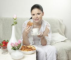 Woman eating croissant and having coffee