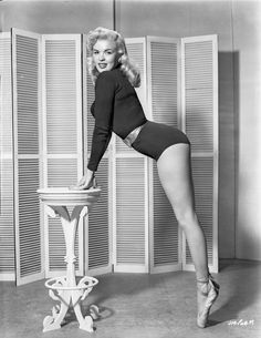 Jayne Mansfield Posed and Bent Over in Black Long Sleeve One Piece Sexy Suit and Silk Waist Belt with Hands on the Table Premium Art Print