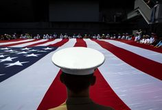 Members of the armed services unfurl a giant flag in the Intrepid museum