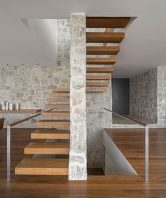Interior in stone and wood offers a blend of contrasting textures - stairs traversing a room  great for the entrance of design we are working on