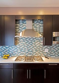 A gorgeous mosaic tile backsplash makes a bold, colorful statement in this contemporary kitchen. Sleek, dark cabinets and stainless steel appliances complete the stylish look.