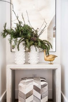 Holiday vignette with fir tree branches in white vases on Thou Swell @thouswellblog