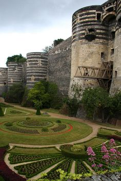The stark but decorative, ancient Chateau d'Angers, castle fortress, built from the 10th to 13th century, in Angers, France, contrasts with the lovely, colorful landscaped gardens.