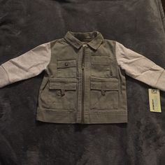 INFANT BOYS JACKET SOFT AND COMFORTABLE ARMY SWEATER STYLE FOR INFANT BOYS BY OSHKOSH. HAS FOUR FRONT POCKETS. COLOR: SATIN TAUPE. Jackets & Coats
