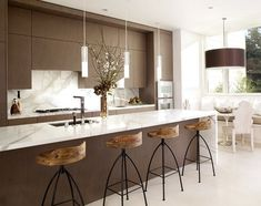 Cocina marrón y blanca con bancos altos de madera y metal