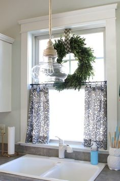 Boxwood wreath on top of small curtains for kitchen window. Have to look into th. Boxwood wreath on top of small curtains for kitchen window. Have to look into this for mine maybe? Farmhouse Kitchen Curtains, Kitchen Sink Window, Kitchen Window Curtains, Farmhouse Windows, Farmhouse Decor, Kitchen Windows, Bathroom Curtains, Window Shutters, Farmhouse Ideas
