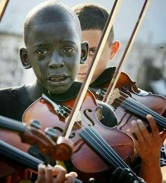 """""""The boy who cries in the photo is Diego Frazao Torquato, who played the violin in the String Orchestra of the Afro Reggae. Afro Reggae is a non-profit organization that gives kids hope and an escape from negative environments. The occasion was the funeral of his social project coordinator, Evandro João Silva, who was murdered in downtown Rio. Diego contracted meningitis at age four, aggravated by pneumonia, and struggled with memory difficulties. He still managed to learn th"""