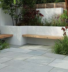 Contemporary hardwood benches built into a white rendered, walled seating/patio area Stonemarket: Garden range: Natural Stone: Trustone Fellstyle Concrete Garden Bench, Garden Paving, Garden Benches, Built In Garden Seating, Backyard Seating, Wood Benches, Garden Tiles, Garden Spaces, Garden Beds