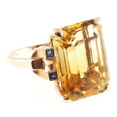 Art Deco Golden Yellow Citrine Sapphire Gold Cocktail Ring. Art Deco Retro pink gold ring with a natural golden yellow 20.00ct Citrine and genuine Sapphire accents. Very good overall condition. The stone is well polished.  1 natural golden yellow Citrine approx. total weight 20.00cts, 19.5 x 14mm, well-polished 4 2mm calibre cut genuine blue Sapphires, approx. total weight .20cts 14K gold