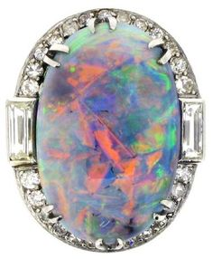 An absolutely magnificent black opal and diamond cluster ring mounted in platinum. Art Deco ring circa 1925 set to centre with an opal weighing approximately 13.00 carats, in a six double claw setting. Set to either shoulder with a close set baguette cut diamond, remainder of diamond border is made up of twenty-six 'eight cut' stones in grain settings. The play of colour in this opal is outstanding. Berganza.