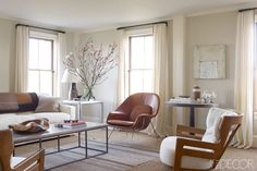 In the living room of this Hamptons weekend retreat, a 1940s chair by Eero Saarinen retains its original leather, the armchairs are by Guillerme et Chambron, and a custom-made sofa is upholstered in an Elizabeth Dow linen; the curtains are of a Calvin Fabrics linen, and the walls are painted in Benjamin Moore's Tapestry Beige. Tour the rest of the home.   - ELLEDecor.com