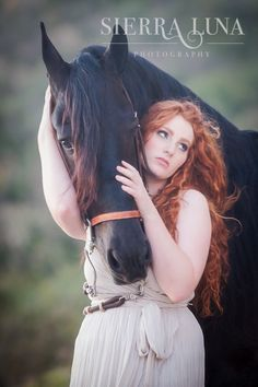 Beautiful redhead and a black horse