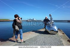 "Helsingor, Denmark - 06 May, 2018: Tourists photographing sculpture ""Han"" of naked young man siting on stone gazing at sea by Elmgrin and Dragset, Sculpture repeats pose of Mermaid in Copenhagen"