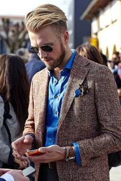 Pairing a brown check wool blazer with dark blue jeans is an on-point option for a day in the office.  Shop this look for $143:  http://lookastic.com/men/looks/long-sleeve-shirt-pocket-square-blazer-jeans-belt-watch/7790  — Blue Long Sleeve Shirt  — Blue Print Pocket Square  — Brown Plaid Wool Blazer  — Navy Jeans  — Brown Leather Belt  — Brown Leather Watch