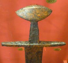 """Alemania. c. 980 - c. 1150. Acero o hierro. Long. Total: 95,3 cm. Long. Hoja: 82,2 cm; Anch.: 5,1 cm; Peso: 1,195 kg. Long. Total: 95,3 cm. Long. Hoja: 82,2 cm; Anch.: 5,1 cm; Peso: 1,195 kg. Pomo en forma de """"nuez del Brasil"""". Wallace Collection A457"""