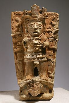 Censer Support, 8th–9th century  Mexico; Maya  Ceramic  H. 21 1/4 in.   This hand-modeled flanged ceramic cylinder would have supported a bowl for the burning of incense for ritual purposes. A high-relief standing figure with a looped motif between his eyes, which is thought to relate to the Maya god of the sun, is depicted on the front. The figure is flanked by two smaller staff-bearing, animal-masked figures shown in profile. All three figures are positioned atop the carapace of a turtle