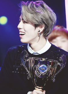 dongwoo's smile holding infinite trophy and sunggyu in the back