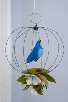 Handcrafted Bird Cage Mobile is a great way to add a pop of color into any kids space.     Constructed from wire, industrial wool felt, ribbon; measures approximately 12 inches tall x 6 inches wide. Very light weight and the bird color can be customized from selection below: maize/ochre, raspberry/salmon, baby blue/ultra blue, white/white