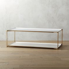 Shop cleo coffee table.   Glossy white enamel, shiny brass and classic box construction—the definition of luxe minimalism.  Inset top and bottom shelves double the storage space of a traditional coffee table.  Useful and beautiful, our favorite.