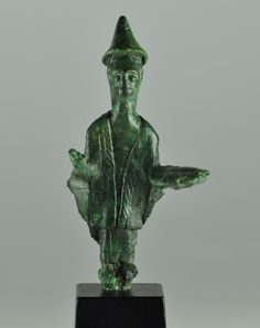 Nuragic bronze priest, 9th-7th century B.C. Nuragic bronze priest, nuragic votive figure representing a priest with in the left hand an offering plate, right hand raised to salute a divinity. wears a hooded long dress, a cape and a stola with engraved decorations, on the head a conical hat, 8.6 cm high. Private collection