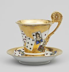 A gilt porcelain Batenin cup and saucer By the Batenin factory, circa 1815‑1830, marked under bases with impressed cyrillic signature 'S.Z.K.B'. Both cup and saucer decorated with motifs of playing cards. Height of cup 13.5 cm.