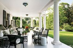 This Miles Redd–designed porch in Greenwich, Connecticut, includes openwork rattan furniture once owned by tobacco heiress Doris Duke and curve-back chairs by IKEA.