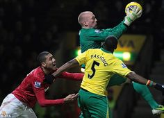 Well held: John Ruddy clings on despite the attentions of Chris Smalling