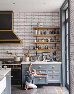 Blue-Gray Kitchen Cabinets, subway tiles, brass detailing and vintage black and brass appliances. WOW