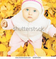Portrait of cute baby outdoor at autumn park with yellow leaves background. Child looking up at camera - stock photo
