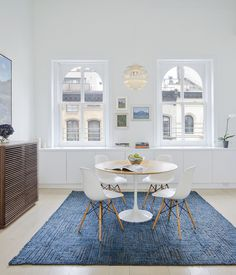In a renovated Tribeca loft, Eames shell chairs surround a Saarinen Tulip table from Knoll. The Line console is from Design Within Reach and the pendant light is Louis Poulsen's Snowball. While architect Matthew Miller of New York firm StudioLAB gutted the space, some of the original details—like the windows—remain. The rug is from ABC Home.