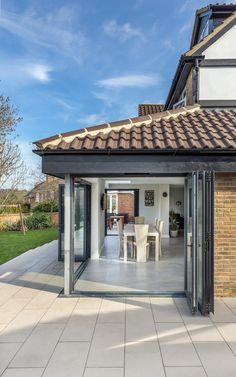 Rear extension | sloped roof | corner opeining | inside outside space | raised patio | garden levels | folding doors | grey aluminium | dining | views through |