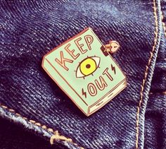 """And stay out! This pretty little teen dream pin is perfect for reminding others to keep out or to put pencil to paper to write down some of your latest trials and tribulations. Wear it on your letterman or fuzzy pink cropped jacket. Each pin is approximately 1"""" x 1"""" wide, rose gold tone metal with a rubber clasp back and two posts for added security."""