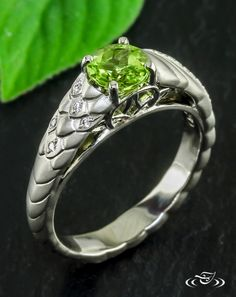 Celtic Dragon Inspired Engagement RingCast in palladium, this Dragon inspired engagement ring holds a radiant peridot center gem. The scales cast along the shoulders and the twisting tail shank are accented with bead set diamonds. Looking through, celtic filigree is prominent in the cathedral of the engagement ring. #Ido #GreenLakeMade #EngagementRing