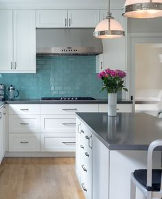 Kitchen with white cabinets, gray countertops, turquoise blue subway tile backsplash | Metson Urman Architecture