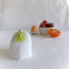 Fresh egg cosy in white linen with colorful tassel. Join us for Dinner at Table Stories