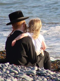 A Hasidic Jewish father and daughter at the beach, watching the waves together