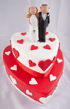 Two tier heart shaped wedding cake in white and red with bride and groom toppers.JPG