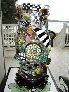 This is a Hurricane Lamp made with Mackenzie Childs glass shards from many of their Circus patterns. The lamp sits on a Rosewood Base and measures 14 from the bottom of the wood base and the top ope