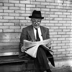 An older man with a hat and Mr Magoo glasses seated on a bench reading The Wall Street Journal in front of a brick wall looking directly at the camera. See a Stunning New Set of Vivian Maier Photos from Eye to Eye   Chicago magazine   July 2014