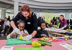 Twee kinderen krijgen tijdens het Blue Food Festival hulp bij het bereiden van de maaltijd.